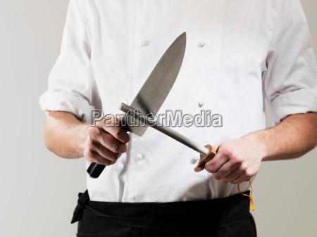 chef sharpening knife against white background