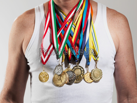 mature man wearing gold medals against