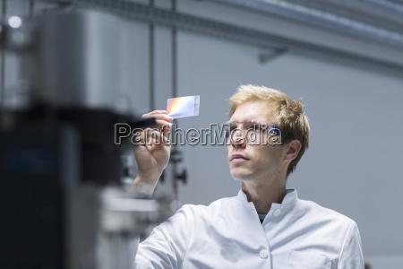 male scientist analysing microscope slide in