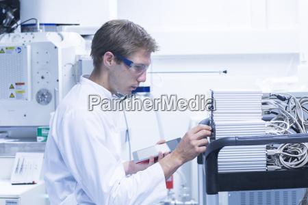 male scientist adjusting control panel in