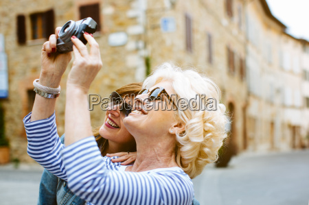 two mature female friends photographing tuscany