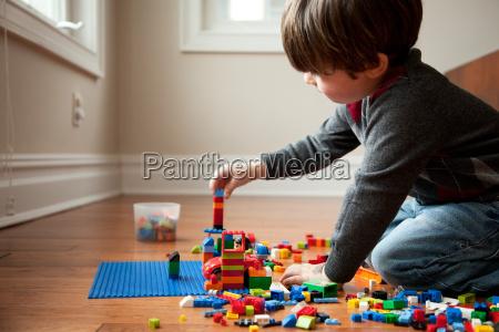 boy playing with plastic blocks