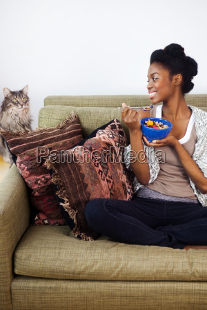 young woman having breakfast looking at
