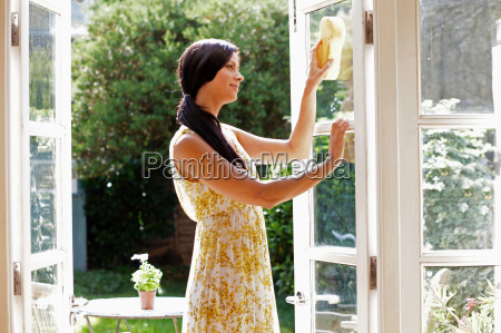 smiling woman cleaning glass doors