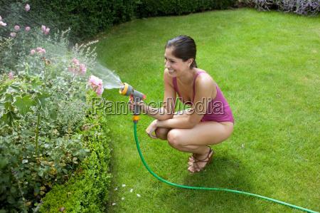 woman in swimsuit watering plants
