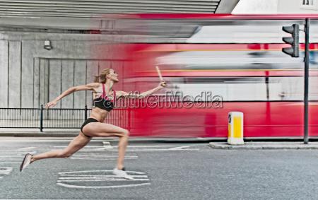 athlete carrying baton on city street