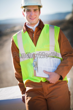man with workvest and clipboard outside