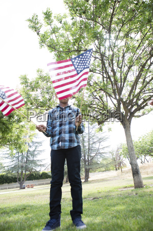 boy holding up american flags in