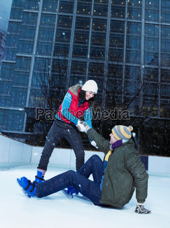 woman helping man up from ice