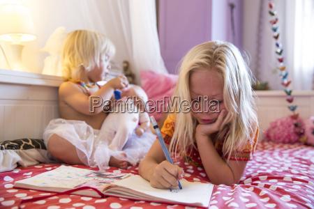 girl and toddler sister lying on