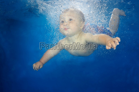 male baby swimming underwater
