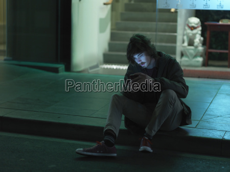 young man sitting on kerb at