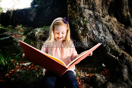 young girl reading a book in