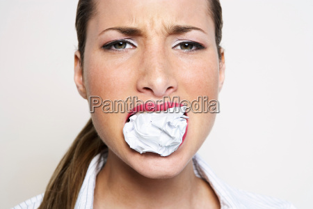 woman with paper ball in mouth