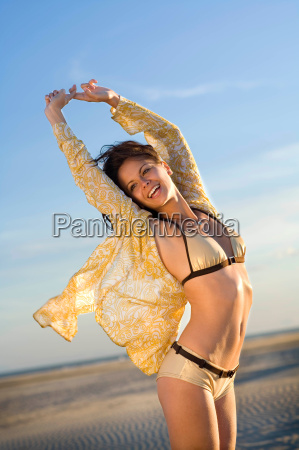 young woman stretches at beach