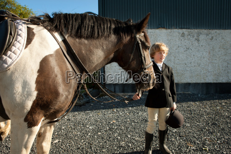 boy holding reins of horse