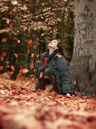 woman throwing autumn leaves into air