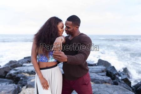 couple standing on rocks beside sea