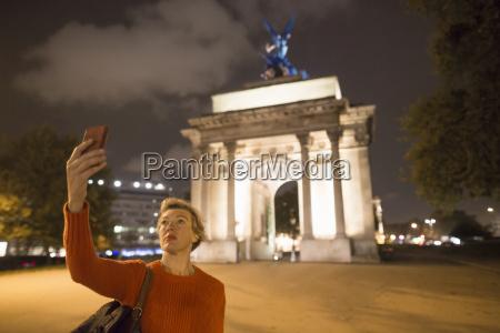 mature female tourist taking smartphone selfie