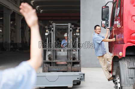 male factory worker guiding forklift truck