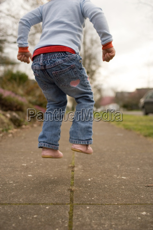 young girl jumping on pavement