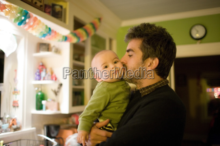 father holding baby boy and kissing
