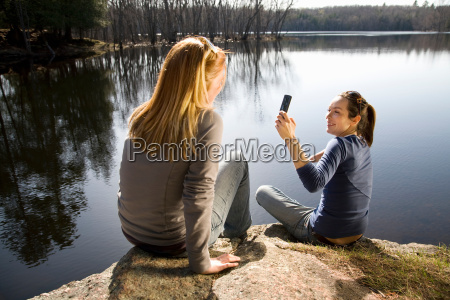 two women taking picture with phone