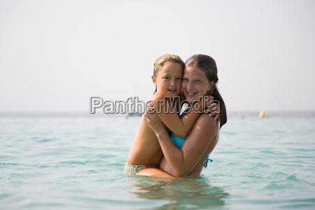 girl hugging little girl in ocean