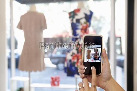mature woman taking photograph of dress