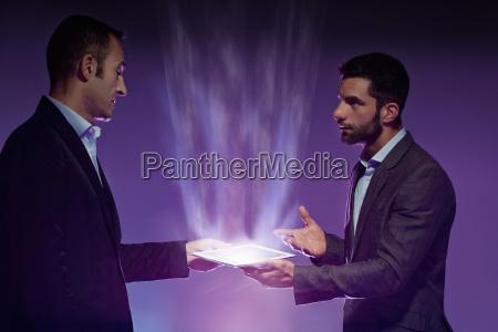 two men holding digital tablet light