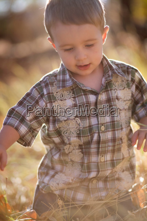 young boy playing in field