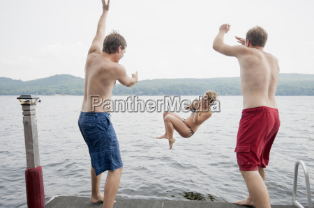 men throwing young woman off jetty