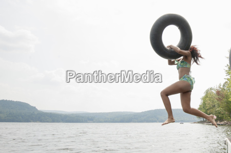 young woman jumping into lake holding
