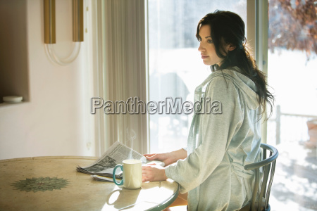 woman with cup and newspaper at