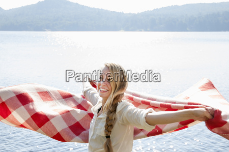 young woman holding blanket by lake