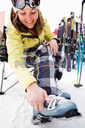 portrait of female skier fastening ski