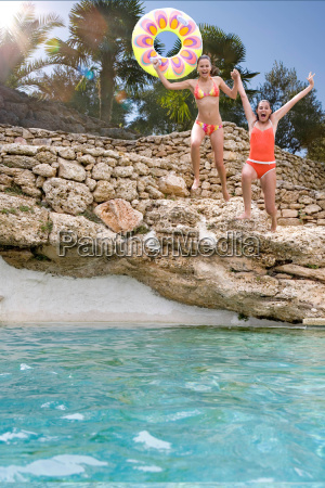 young women jumping into stone pool