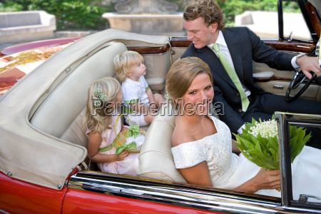 wedding couple with children in car