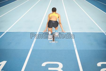 junge athletin auf startbloecken rueckansicht