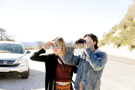 young couple by car on mountain