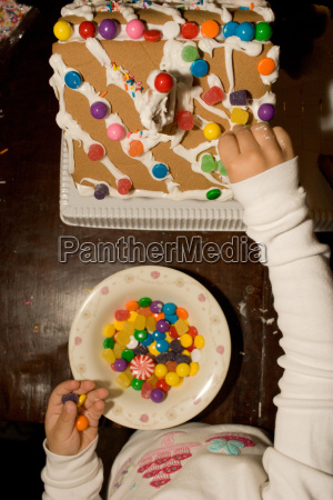 young girl decorating gingerbread house