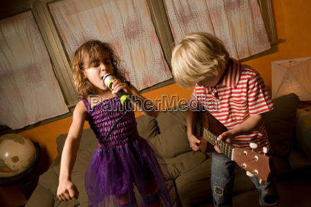 girl singing with microphone with boy