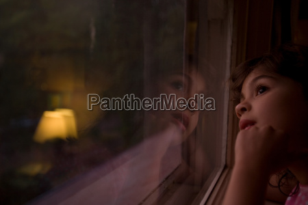 young girl looking through window