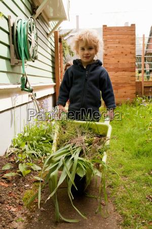 young boy pushing wheelbarrow full of
