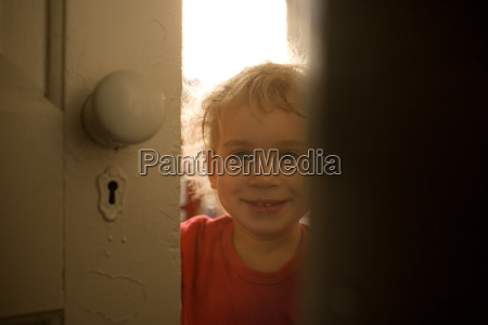 toddler boy looking through gap in