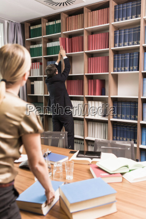 woman watching man removing book from