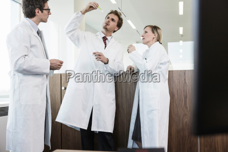 three people wearing lab coats looking