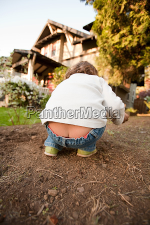young girl bending in garden