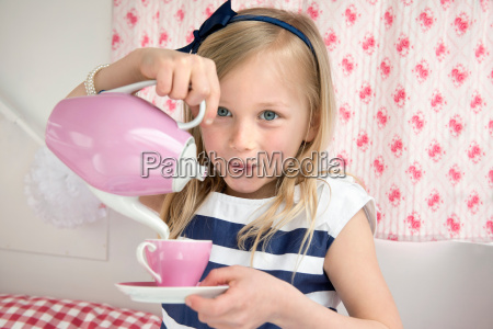 portrait of young girl pouring tea