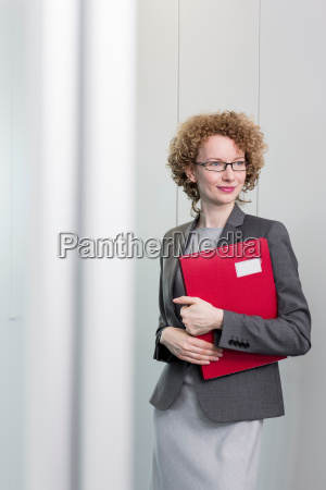 portrait of businesswoman holding red file